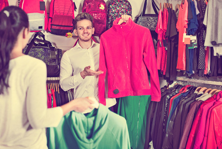 sleeveless hoodie: Young glad couple choosing new sportswear in sports store