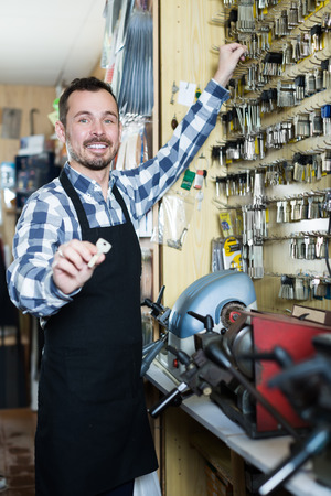attentiveness: Smiling male worker demonstrating result of his key forming in workplace Stock Photo