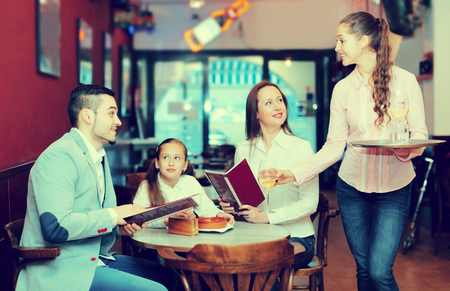 Young waitress and cheerful family with daughter reading menu. Focus on the waitress Stock Photo