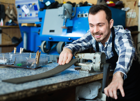specialized job: Young diligent friendly smiling male worker using his tools for repairing in specialized workshop