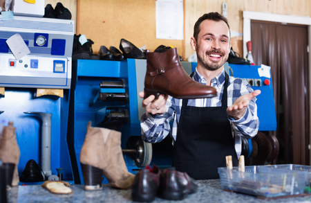 resulted: Young  friendly  male worker demonstrating repaired shoes in shoe repair workshop