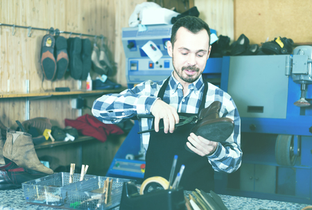 specialized job: Young man worker working at restoring shoe in repair workshop