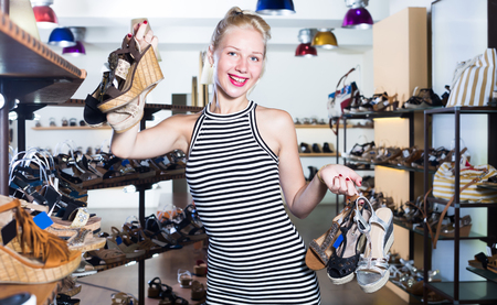 Female customer holding many pair of heeled shoes in fashion store
