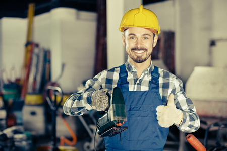 neatness: Smiling working man practicing his skills with power jigsaw in the workshop Stock Photo