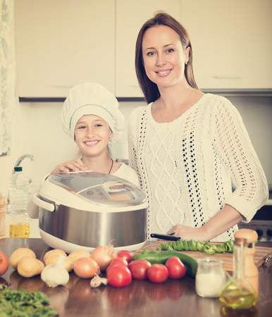 Portrait of smiling girl and her mom with rice cooker at home kitchen Stock Photo
