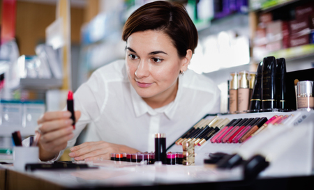 Young cheerful positive female customer searching for reliable make-up products in pharmacy