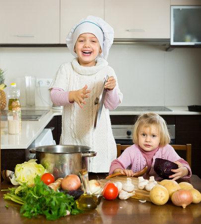 Two joyful little sisters learning how to cook at domestic kitchen