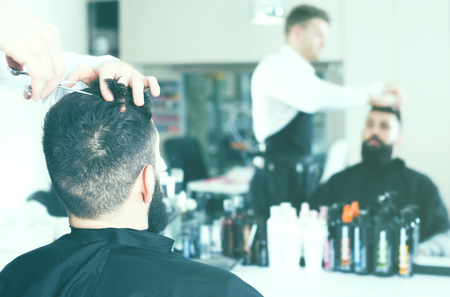 coiffeur: professional male stylist creating new haircut for man client at hairdressing salon Stock Photo