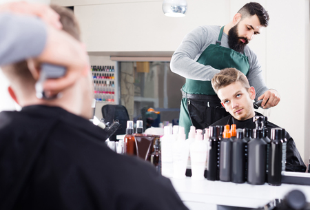 scandalous: Young english client feeling discontent about his new haircut at hair salon