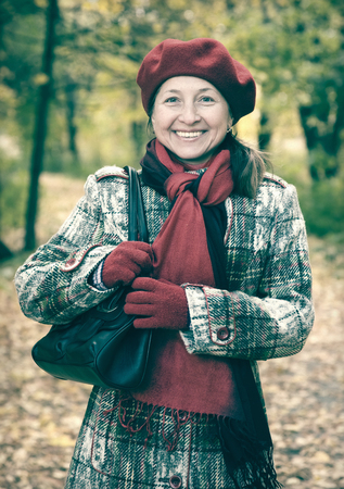 Portrait of senior woman  in autumn park Stock Photo