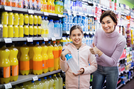 Glad cheerful smiling female shopper with teenage daughter searching for beverages in supermarket
