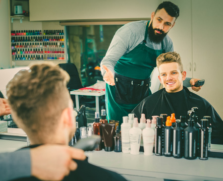 coiffeur: calm guy stylist creating new haircut for man client at hairdressing salon