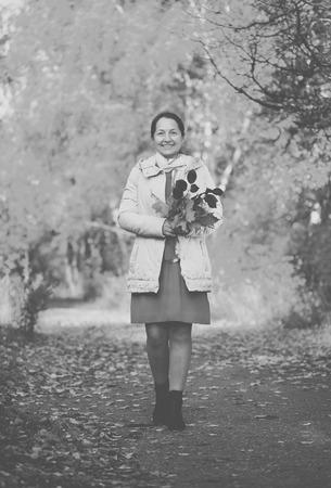 walking mature woman in autumn park Stock Photo