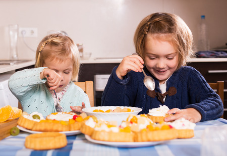 5s: Two european girlfriends eat tasty cream pies in kitchen table