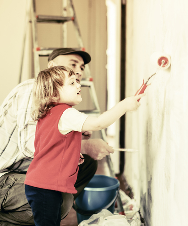 modifying: child  with father paints wall  at home
