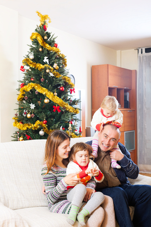 red sofa: Happy family of four celebrating Christmas in living room Stock Photo