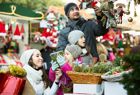 Cheerful parents with two little children buying flower and coniferous decorations for Christmas. Focus on girl