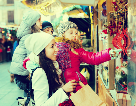Family with children purchasing Christmas decoration and souvenirs at a fair. Focus on women