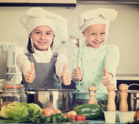 kin: Two small smiling happy girls cooking vegetable soup at home kitchen Stock Photo