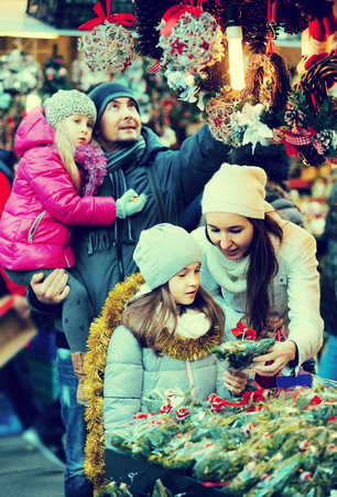 Happy family of four choosing decorations at market. Focus on woman and girl