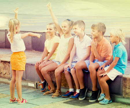 portrait of smiling russian  children spending time outside and playing charades Imagens