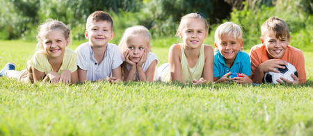 portrait of smiling russian children lying on grass in park and looking happy
