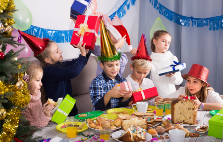 happy russian children presenting gifts during Christmas dinner Stock Photo