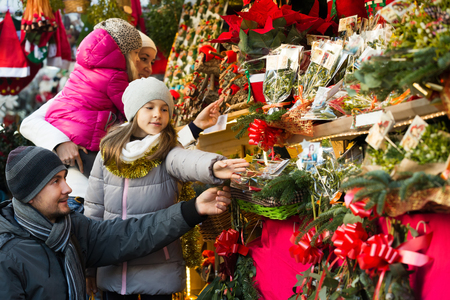 Happy family of four choosing floral christmas decorations at market. Focus on man and girl