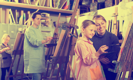 Glad girls admiring work of their group made during painting class at art studio Stock Photo