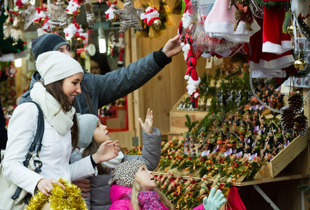 5s: Happy family of four buying holidays decorations at Christmas market together Stock Photo