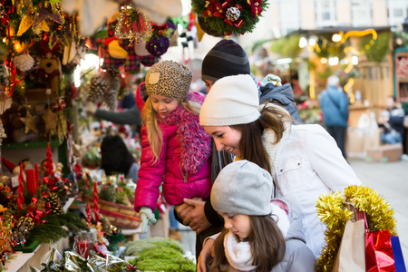 Young parents with two little daughters choosing X-mas decorations in market. Focus on woman