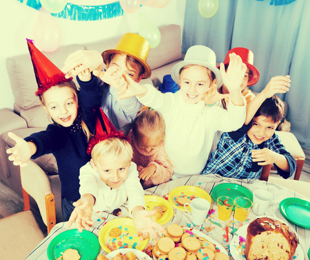 Positive group of children having fun during friend's birthday party at his home Stock Photo