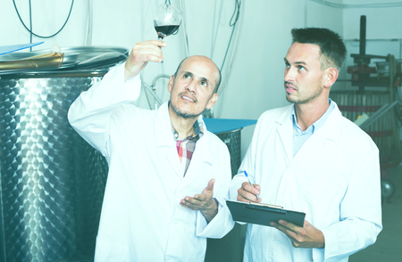 Two workers wearing coats standing with glass of wine in fermenting section