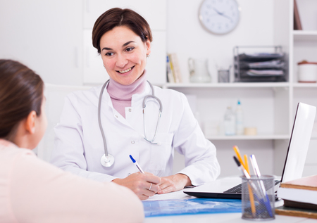 advise: Doctor fills patients card for girl and asks her about health in medical office