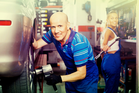Smiling glad diligent mature male technician fitting new car tyre at service station
