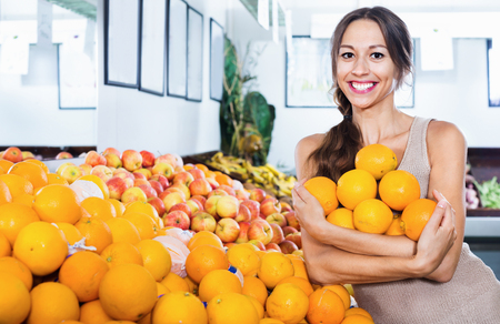 Positive cheerful  woman buying oranges on marketplace