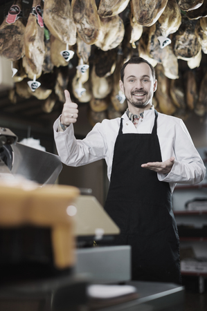 substantial: Young male seller offering displayed sorts of meat in butcher's shop Stock Photo