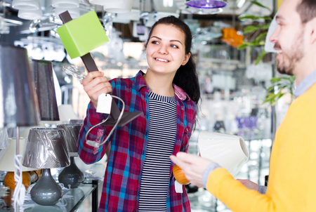 smiling european man and girl in lighter shop choosing stylish and modern lamp for house interior Stock Photo