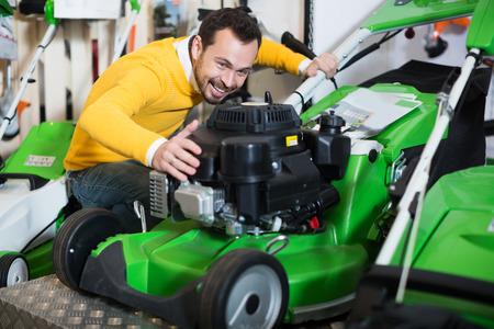 Attractive young  man choosing lawnmower in garden equipment shop