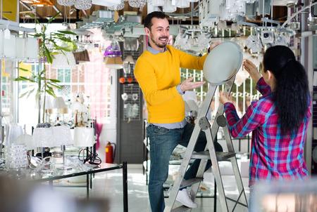 matt: Woman and man in lighter shop are choosing stylish round matt glass ceiling lamp.
