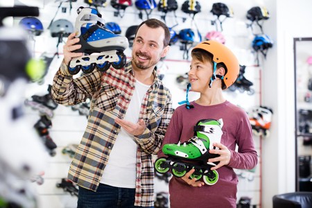 boasting: Cheerful man and son boasting purchased roller-skates in sports store Stock Photo