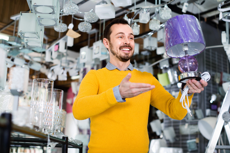 Young happy cheerful positive man in shop of home appliances choosing modern and stylish lamp for home interior