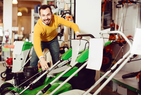 Male customer is considering a range of lawnmowers in a supermarket Stock Photo