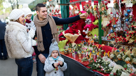 5s: Positive  family of four choosing Christmas decorations at market.