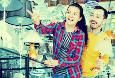 Young couple in shop of home appliances choosing modern and stylish lamp for home interior