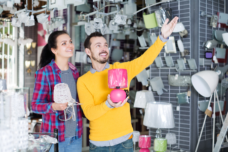 wall sconce: Glad young man with girl in lighter shop points to interesting model lamp