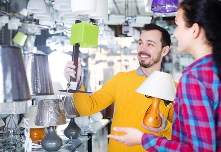 Happy adult man and girl in lighter shop choose table lamp for house Stock Photo