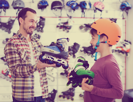 purchased: Laughing father and boy boasting purchased roller-skates in sports store Stock Photo