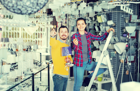 brightness: Young man and a woman are looking for a chandelier for a house in a supermarket