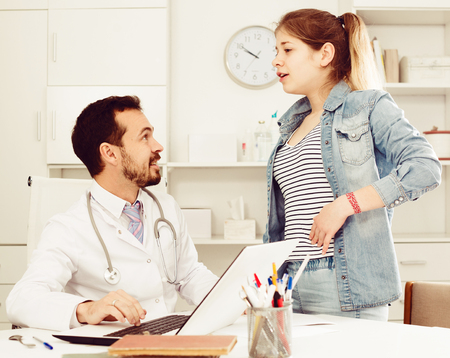 Teenage female visitor consulting male doctor about pain in side in hospital Stock Photo